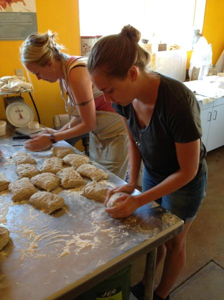 Heather (foreground) preparing loaves of bread